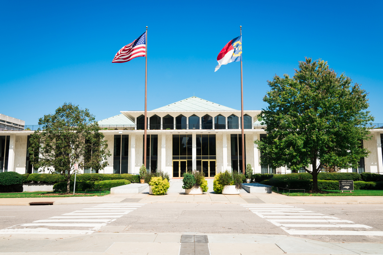 """North Carolina Legislative Building with American and North Carolina Flags in the wind. The North Carolina State Legislative Building is the meeting place of the North Carolina General Assembly, the state legislature of the U.S. state of North Carolina. Raleigh, North Carolina, USA"""